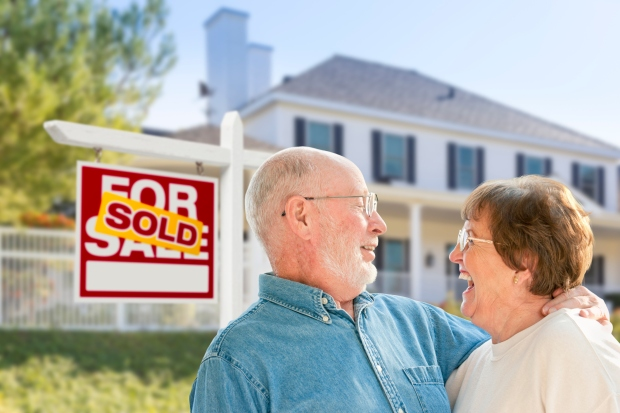 Senior-Couple-in-Front-of-Sold-Real-Estate-Sign,-House-525496455_2122x1415.jpeg
